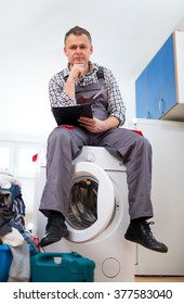 Repairman is repairing a washing machine on the white background. Entering malfunction sitting on washing machine.
