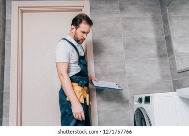 repairman with toolbelt and clipboard checking washing machine in bathroom