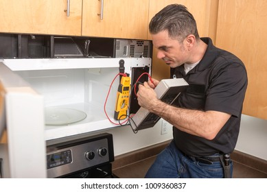 Repairman troubleshooting a microwave with voltage meter.
