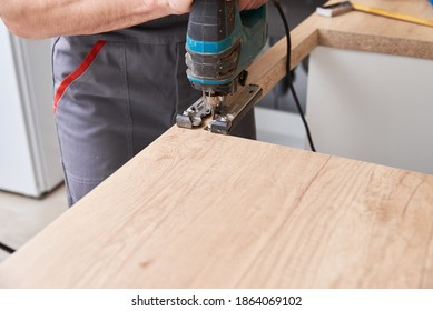 Repairman using electric jigsaw. Sawing place for installing gas hob in a worktop