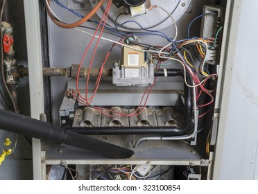Repairman vacuuming inside of a gas furnace during a cleaning.