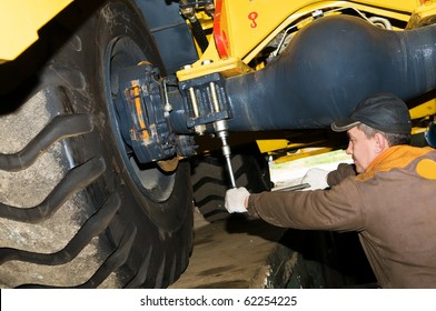 repairman worker screwing nuts of axle assembly in heavy wheel loader