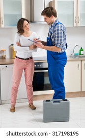 Repairman Writing On Clipboard While Beautiful Woman Standing In Kitchen