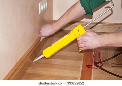 Repairman's hands Installing Skirting Board Oak Wooden Floor with Caulking Gun Silicone from Cartridge. Flooring with Wooden Batten Repair.