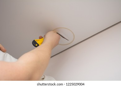 repairmen install stretch ceiling made of pvc vinyl film using a gas heat gun