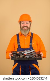 Repairment tools. Worker holds repair tools. Building. Industry. Technology. Spanner. Bearded builder. Builder in construction helmet. Hard hat. Industrial worker. Repair. Hammer. Screwdriver.