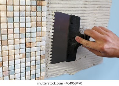 Repairs in the apartment: installing mosaic tile on wall. / A worker covers the wall with adhesive using a notched trowel.