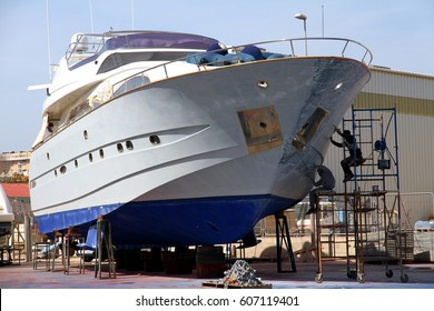 Repairs on the fiber of the hull of a yacht in the shipyard.