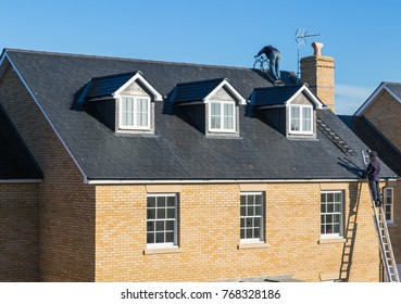Repairs taking place to a slate roof on a brick house with three dormer windows. Men roofers are on high ladders. One man is on top of the roof.  There s a chimney and television aerial on the roof