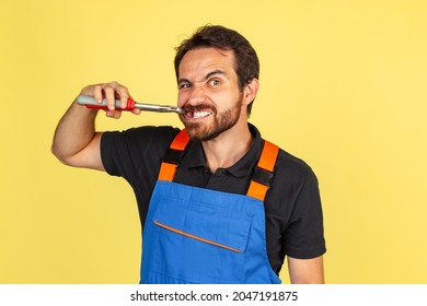 Repearing teeth. Half-length portrait of smiling young bearded man, male auto mechanic wearing blue work dungarees isolated over yellow studio background. Concept of funny meme emotions, ad, job