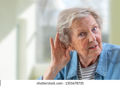 Repeat, please. Close-up of face of charming elderly woman is holding hand by her ear and struggling to hear something