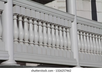 Repeated design of front porch spindles in bright contrast.