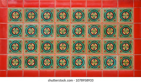 Repeating pattern of ceramic tiles with a geometric floral design, with a red border.