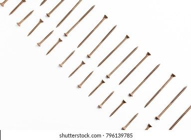 A repeating pattern of long and short wood screws on an isolated white background.
