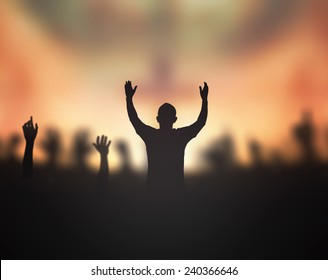 Repentance concept: Silhouette christian raising hand for worship God on blurred cross background