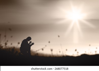 Repentance and worship concept: Prayer kneeling and praying to God on mountain autumn sunset background