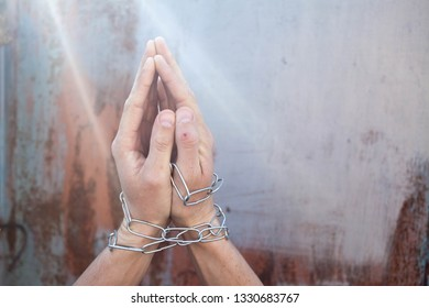 Repented man prisoner with his hands shackled in chains