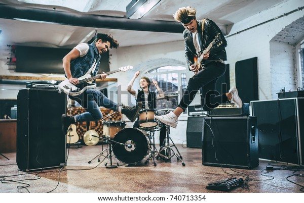 Repetition of rock music band. Bass guitar player, electric guitar player and drummer behind the drum set. Rehearsal base