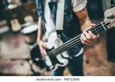 Repetition of rock music band. Cropped image of bass guitar player. Rehearsal base