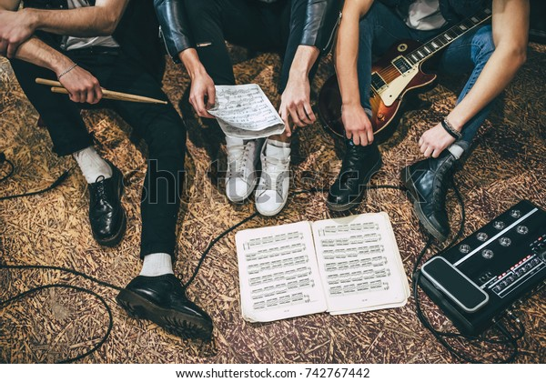 Repetition of rock music band. Cropped image of guitar players and drummer are sitting on the floor at rehearsal base with notes. Top view