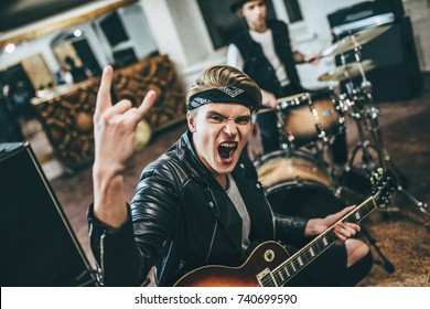 Repetition of rock music band. Electro guitar player and drummer behind the drum set at rehearsal base. Showing the sign of horns.