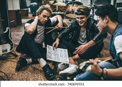 Repetition of rock music band. Guitar players and drummer are sitting on the floor at rehearsal base with notes.