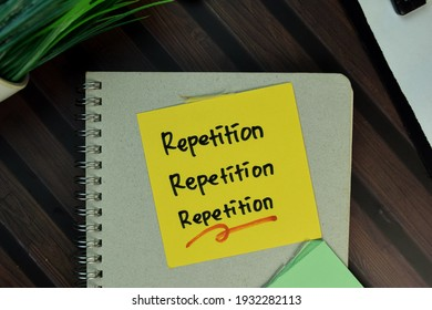 Repetition, Repetition, Repetition write on sticky notes isolated on Wooden Table. Selective focus on Repetition text