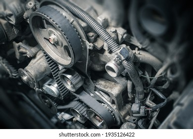 Replacement timing belt with rollers on the old diesel engine in a car service. Close up. Blur effect.