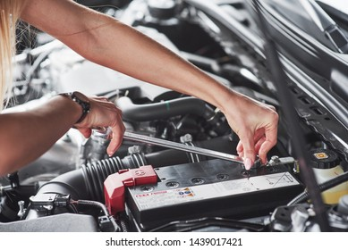 Replacing the battery. Car addicted woman repairs black car indoors in garage at daytime.