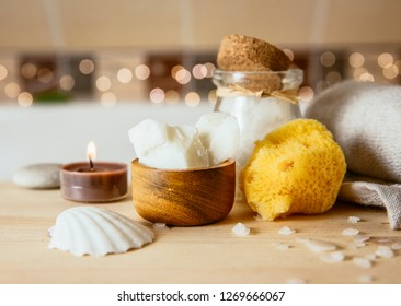 Replacing cosmetic products with natural coconut oil moisturizer cream. Solid coconut oil chunks in small wooden cup with other bath body care products in beige brown tile bathroom. Cozy set bokeh.
