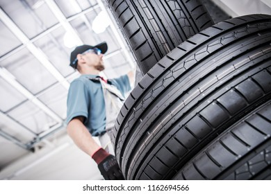 Replacing Old Car Tires. Vulcanization Service Worker and New Tires.