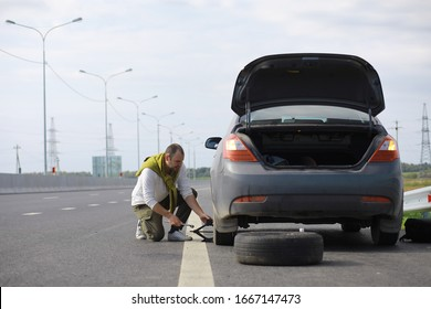 Replacing the wheel of a car on the road. A man doing tire work on sidelines.
