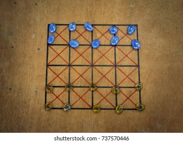 A replica ancient board game using glass beads as playing pieces.