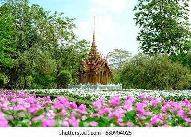 Replica Thai palace with beautiful white and pink flowers on foreground and bright clear blue sky with green trees on background,