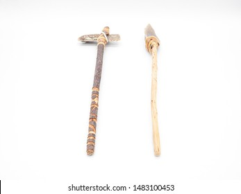 Replicas of the primal stone tools with wooden handles and leather strapping isolated on white background. Primitive stone axe and dagger or spear: weapons of the prehistoric peoples. Perspective view
