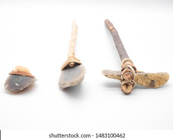 Replicas of the primal stone tools with wooden handles and leather strapping isolated on white background. Primitive stone axe, dagger and hammer: weapons of the prehistoric peoples.Selected focus.