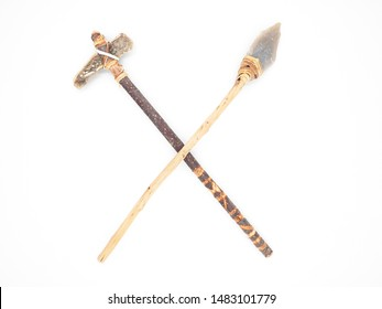 Replicas of the primal stone tools with wooden handles and leather strapping isolated on white background. Crossed primitive stone axe and dagger or spear: weapons of the prehistoric peoples.