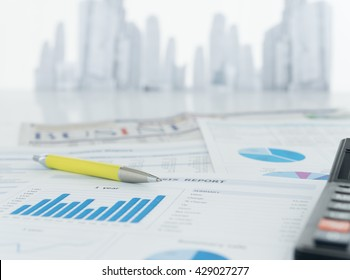 The report analyzes the growing business ,pen, calculator, newspaper on desk of financial adviser with city in background.
