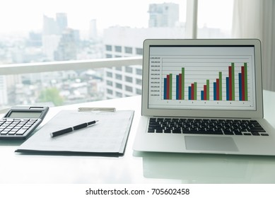 The report summarizes the result of business operation on computer screen on desk of investor.