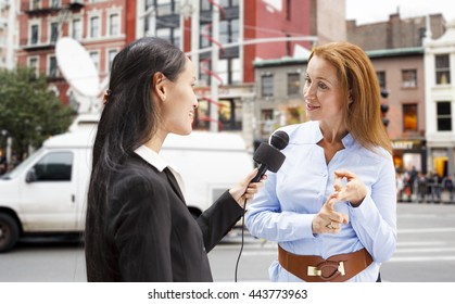 A reporter with a microphone interviews a woman in New York City with a news van in the background.