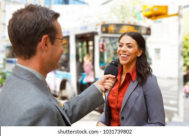 A reporter with a microphone interviews a woman on a city street  with a bus in the background.