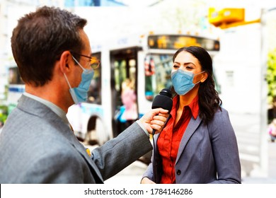 A reporter with a microphone interviews a woman on a city street. Both are wearing face masks.  There is a bus in the background.