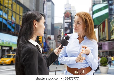 A reporter with a microphone interviews a woman in Times Square New York City.