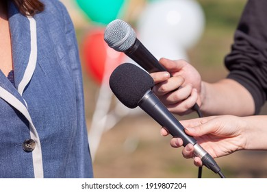 Reporter at news conference holding microphone making media interview with female politician or business woman
