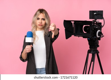 Reporter woman holding a microphone and reporting news over isolated pink background showing thumb down with negative expression