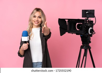 Reporter woman holding a microphone and reporting news over isolated pink background shaking hands for closing a good deal