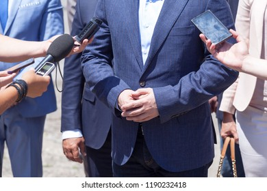 Reporters making media interview with unrecognizable businessman or politician