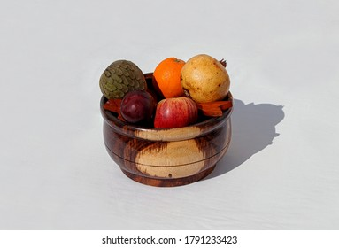 representation of the deity known as Shango, of the Yoruba religion, wooden cauldron with wooden tools, and fruit offering, photographed on white background
