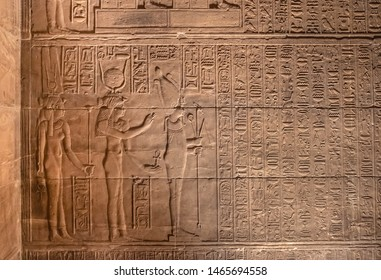 Representation of goddesses Isis and Hathor with god Osiris on the wall with hieroglyphs at Philae temple near Aswan, Egypt