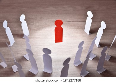 Representation of person preaching in front of a group of people by means of paper cutouts in the shape of a person on wooden table elevated view - Shutterstock ID 1942277188